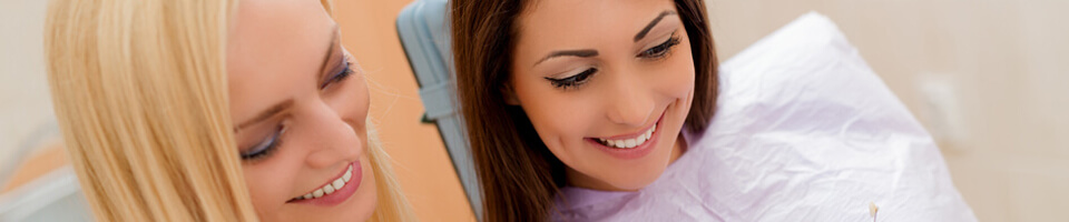 Patient and dental assistant smiling