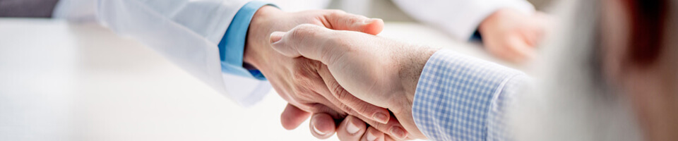 Partial view of senior patient and doctor shaking hands