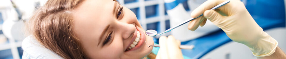 Female patient smiling at dentist seated on dental chair